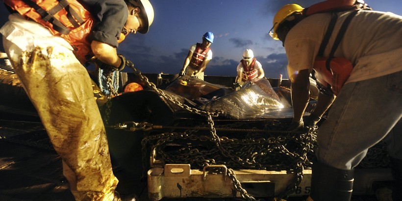 """Crew members from Marine Vessel Braxton Perry recover a deflection boom after three days of controlled burns in the Gulf of Mexico in this May 7, 2010 photograph. The U.S. Coast Guard working in partnership with BP PLC, local residents, and other federal agencies is conducting """"in situ burning"""" to aid in preventing the spread of oil following the April 20 explosion on Mobile Offshore Drilling Unit Deepwater Horizon. Picture taken on May 7, 2010.     REUTERS/Justin Stumberg/U.S. Navy photo/Handout    (UNITED STATES - Tags: ENVIRONMENT DISASTER) FOR EDITORIAL USE ONLY. NOT FOR SALE FOR MARKETING OR ADVERTISING CAMPAIGNS - RTR2DMXF"""